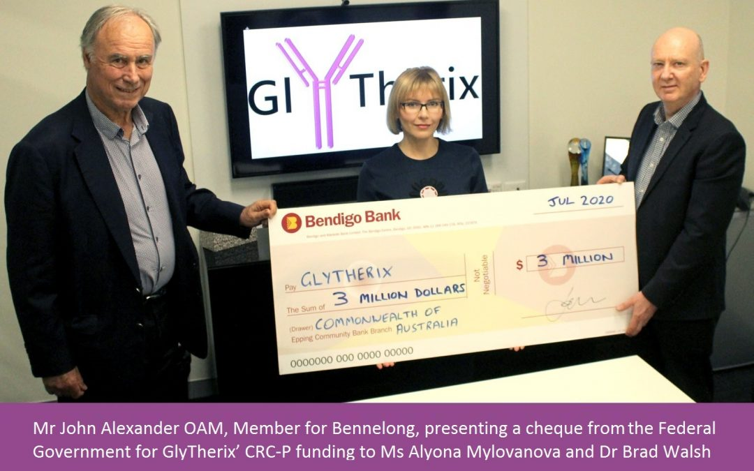 Mr John Alexander OAM, Member for Bennelong, presenting a cheque from the Federal Government for GlyTherix' CRC-P funding to Ms Alyona Mylovanova and Dr Brad Walsh